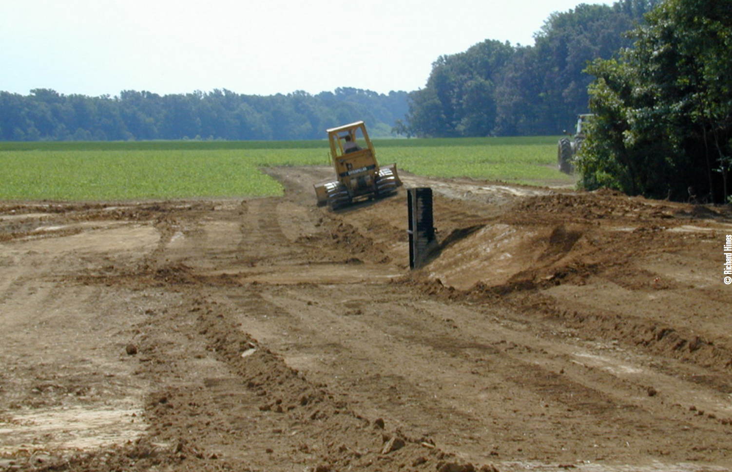 Bulldozer creating a levee for a waterfowl wetland