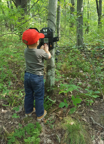 boy checking game camera