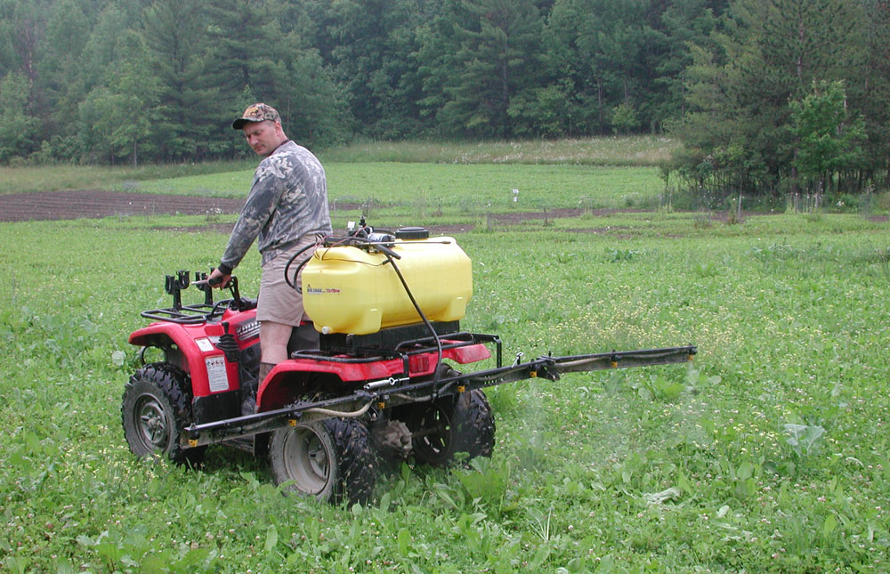 spraying a clover field with ATV